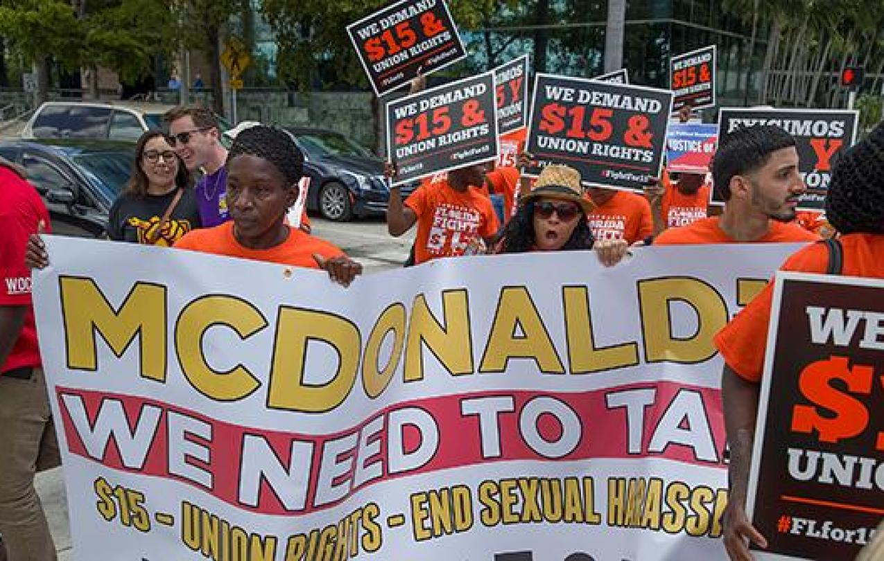 """Supporters of the """"Fight for $15"""" movement march with banners and posters."""